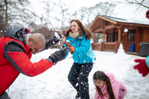Throwing Snowballs at her Husband A woman throws a snowball at her husband. In the background their log cabin can be seen. ski holiday stock pictures, royalty-free photos & images