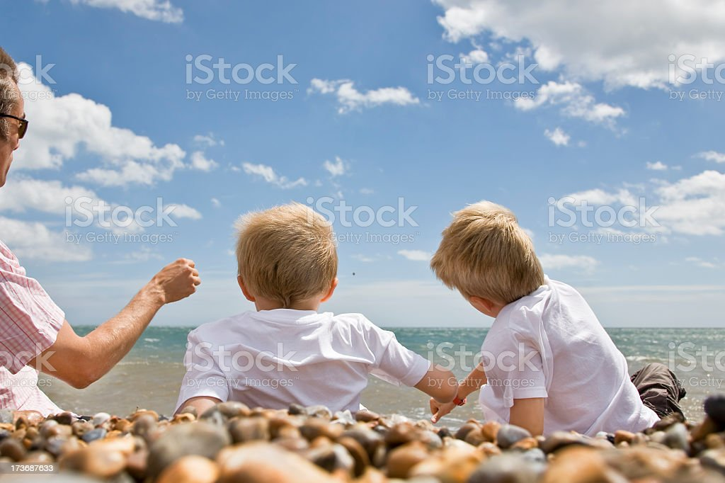Throwing stones with dad on sunny day at beach stock photo