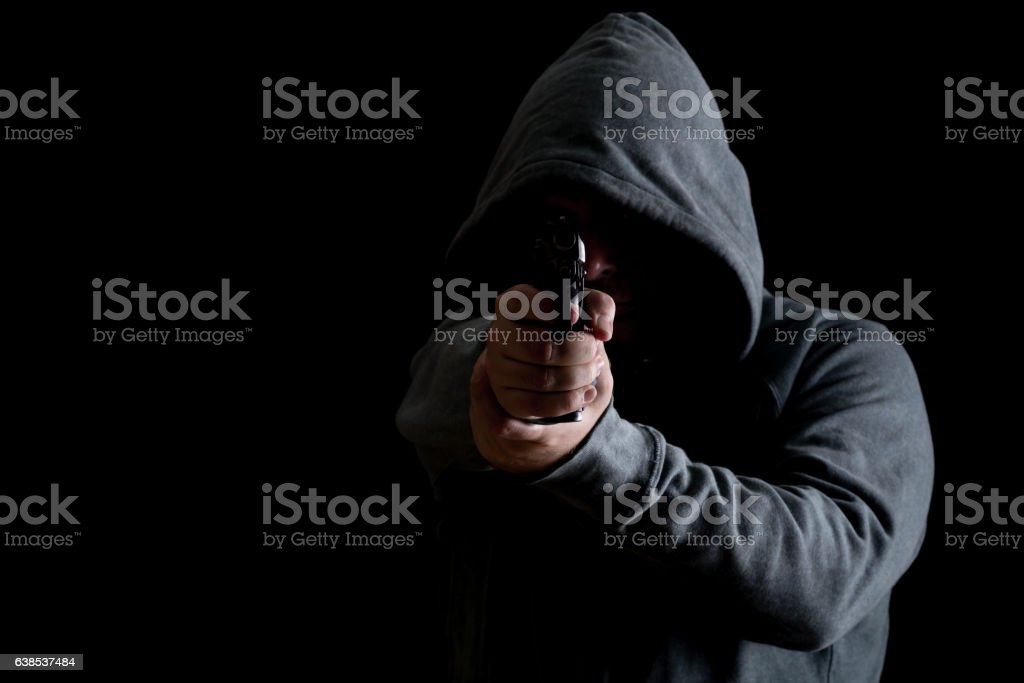 Thug in hoodie points gun stock photo