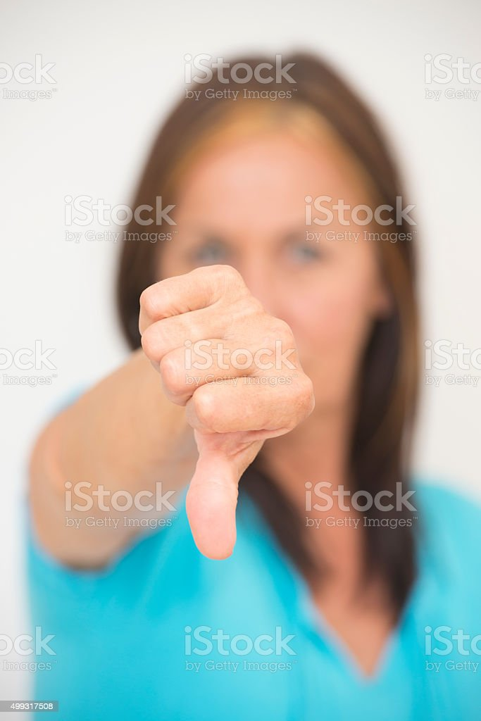 Thumb down gesture of negative woman stock photo