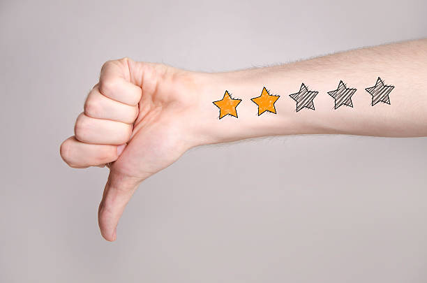 Thumb down with two star rating Mans hand showing thumb down and two star rating tattoo like drawing on gray background, internet rating concept  negative emotion stock pictures, royalty-free photos & images