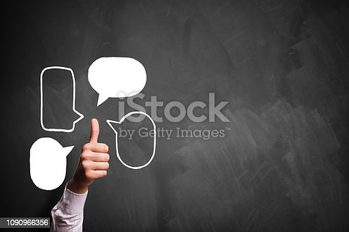 693589426istockphoto thumb up gesture with speech bubble symbols in front of a blackboard 1090966356
