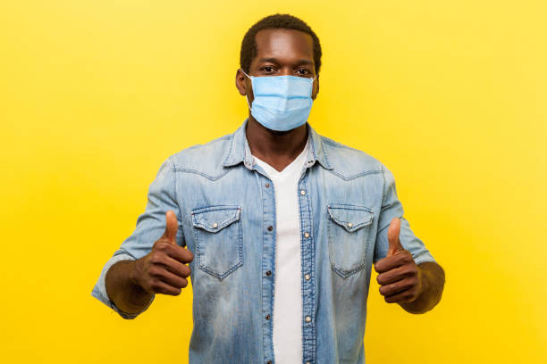 Thumbs up, excellent job! Portrait of enthusiastic handsome man in denim casual shirt with surgical medical mask smiling and showing like gesture at camera. stock photo