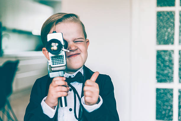 Thumbs up from boy shooting video with retro camera stock photo