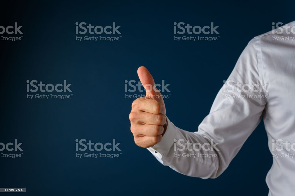 Thumbs up gesture Businessman making a thumbs up gesture over a navy blue background. Achievement Stock Photo