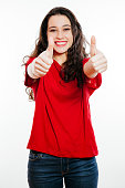 Young positive bruentte woman showing thumbs up smiling. Isolated on white