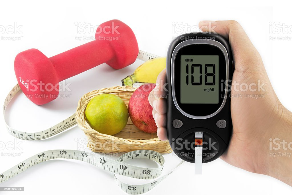 Thumbs up, glucometer and fresh fruits with tape measure. stock photo