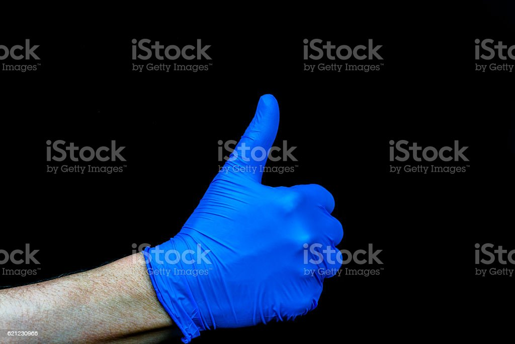 Thumbs up. Hand with blue medical glove. stock photo