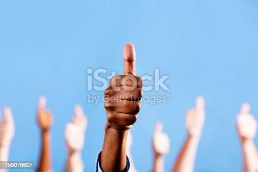 istock Thumbs up! Male African-American hand gestures, others in background 155076607