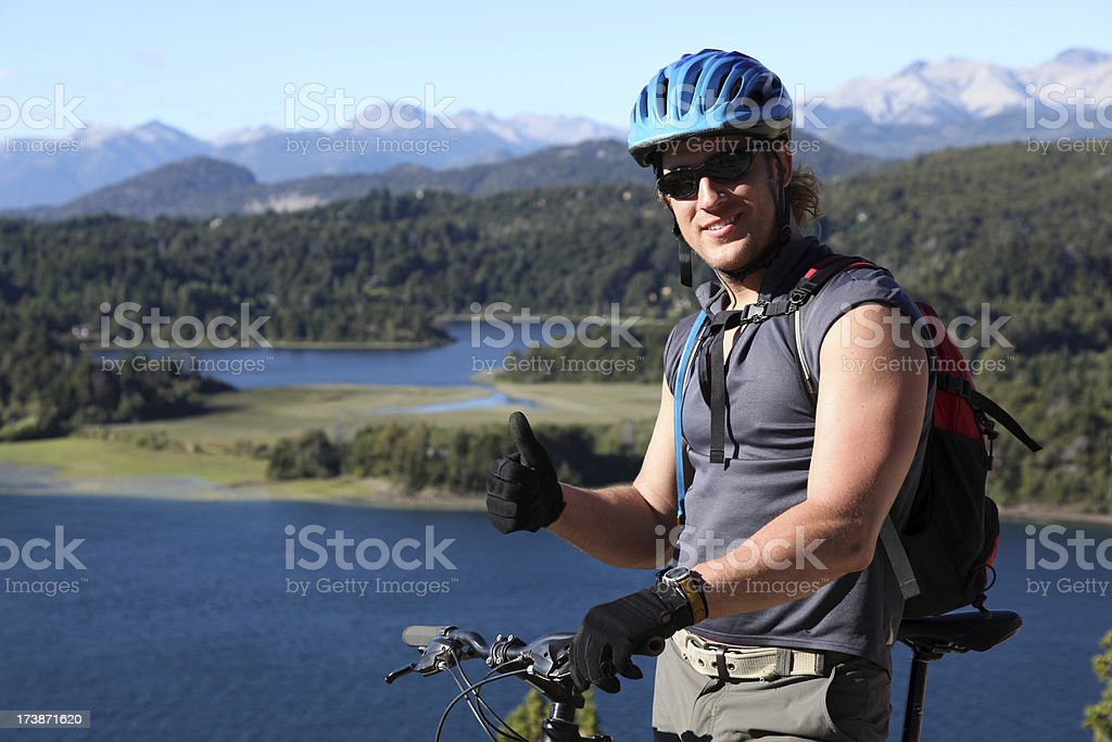 Thumbs Up man Mountain Biker with Mountains and Lake Background royalty-free stock photo