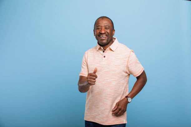 Thumbs Up! Portrait of a man standing in front of a blue studio background smiling at the camera while holding his thumb up. 65 69 years stock pictures, royalty-free photos & images