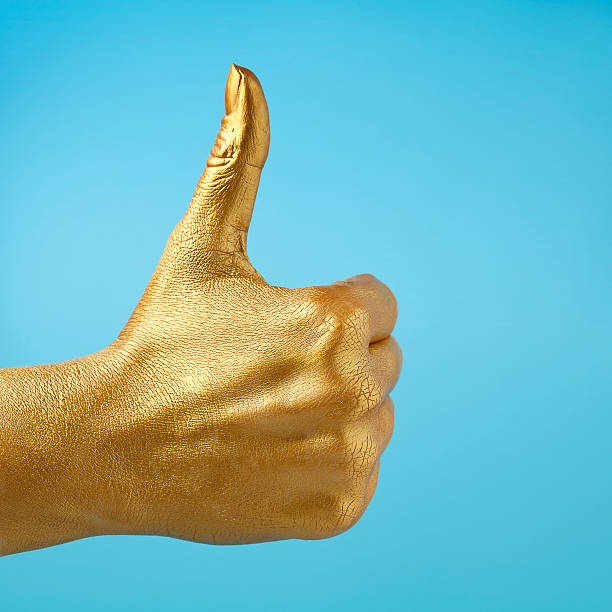 thumbs up gold painted hand giving thumbs up sign body paint stock pictures, royalty-free photos & images