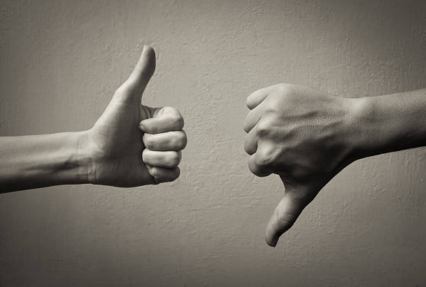 Thumbs up thumbs down. Yes and no concept.  negative emotion stock pictures, royalty-free photos & images