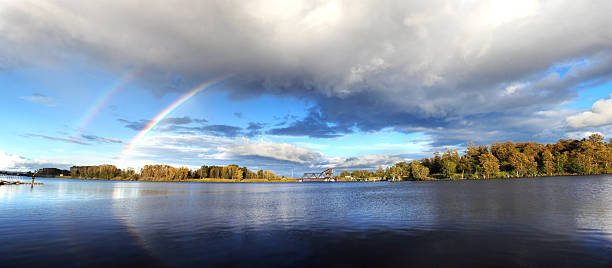 Thunder Bay Rainbow A rainbow briefly appeared in one of the Thunder Bay parks. Photo taken in late August at sunset. A figure of a fishing person can be seen on the left side of the picture. rainbow bridge ontario stock pictures, royalty-free photos & images