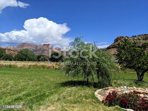 Thunder storm building over The Watchman Peak in Zion National Park as seen from over green pastures in Rockville Utah
