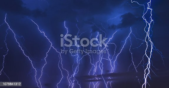 656192770 istock photo Thunder storm lightning strike on the dark cloudy sky background at night. 1075841312