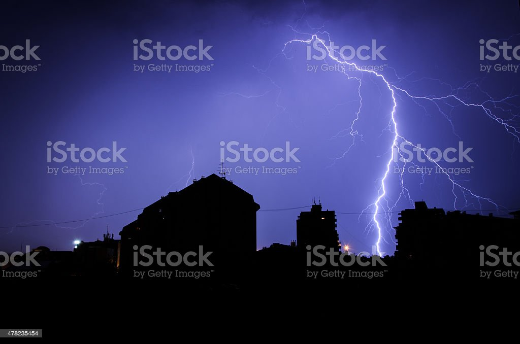 Thunderbolt over the buildings, silhuette stock photo