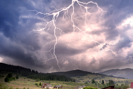 Storm clouds in the Alps after a strong thunderstorm with lightning and thunder over the tops of the ridges, with wind and rain