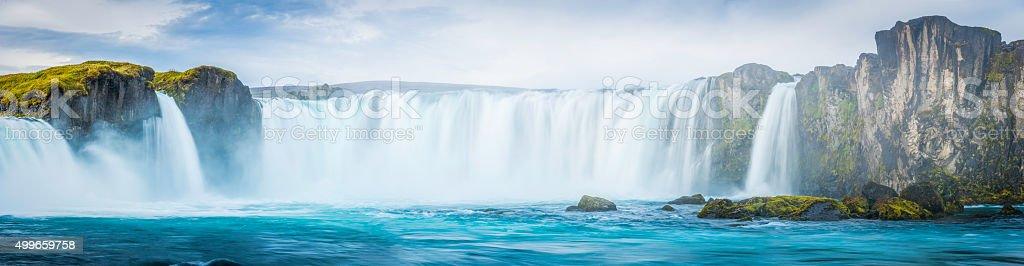 Thundering waterfalls cascading into blue mountain river panorama Godafoss Iceland stock photo