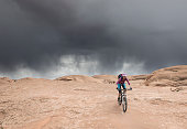 A lonely female mountainbiker in front of an oncoming thunderstorm at the famous Slickrock Trail nearby Moab which is a city on the southwestern edge of Grand County in eastern Utah in the western United States. Moab attracts a large number of tourists every year, mostly visitors to the nearby Arches and Canyonlands national parks. The town is a popular base for mountain bikers who ride the extensive network of trails including the Slickrock Trail, and for off-roaders who come for the annual Moab Jeep Safari.\nCanon EOS 5D Mark IV, 1/250, f/13, 35 mm.