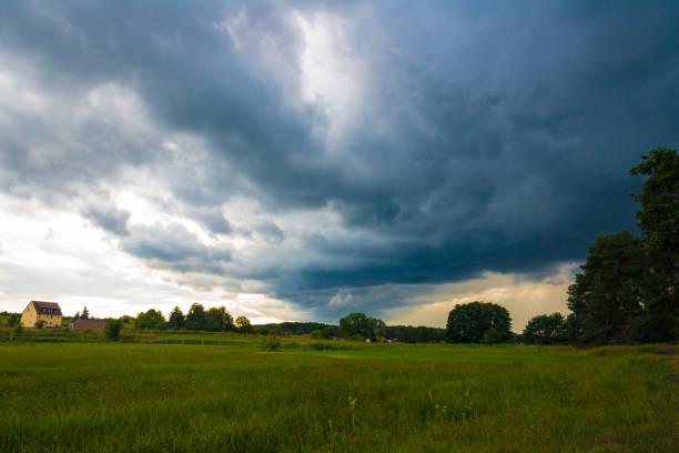 gewitterfront mit dunklen wolken über wiesen - wettervorhersage deutschland stock-fotos und bilder