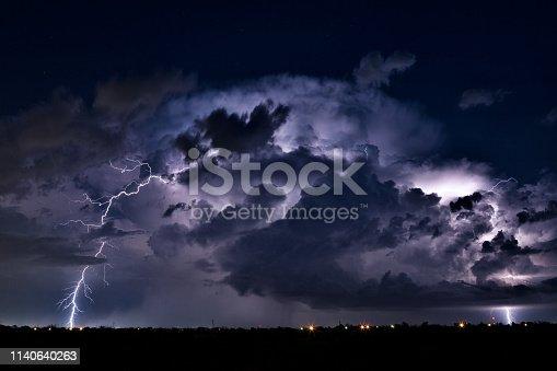 Thunderstorm cumulonimbus cloud illuminated by lightning bolt strikes.