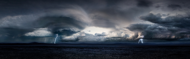 Digitally generated dramatic and majestic panoramic landscape of a thunderstorm in a large desert during the day.