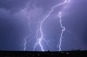 Thunderstorm with lightning bolt strikes and storm clouds in the sky at night.
