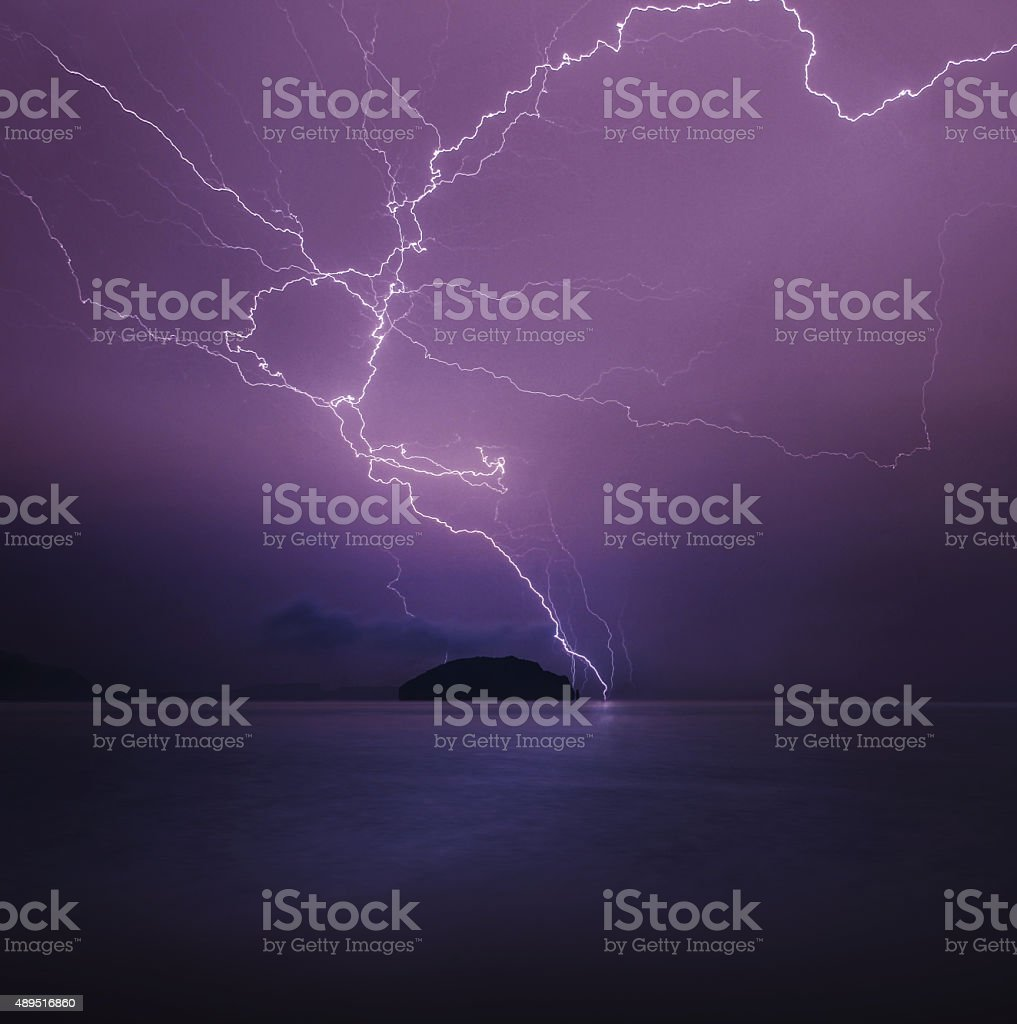 Thunderstorm over the sea with island stock photo