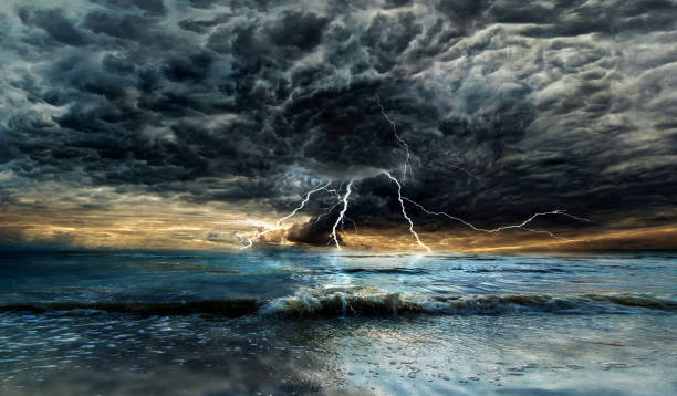 Thunderstorm with lightning above the sea at sunset stock photo