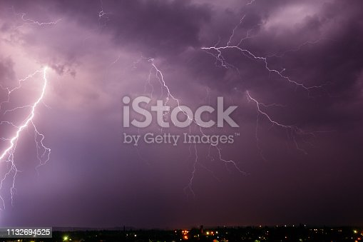1155214300istockphoto Thunderstorm with lightning in the sky over a small town 1132694525