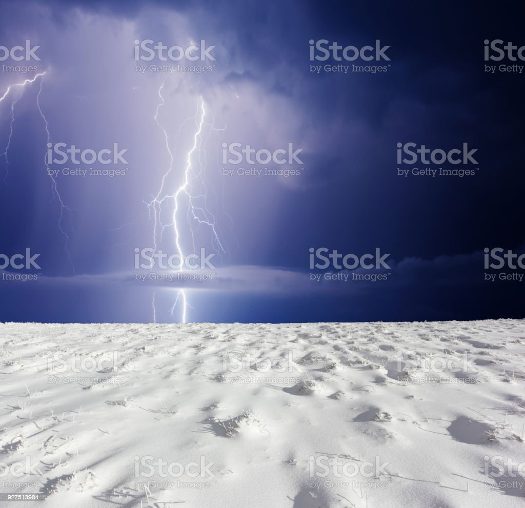 Thunderstorm with lightning in winter meadow. Dark ominous clouds.