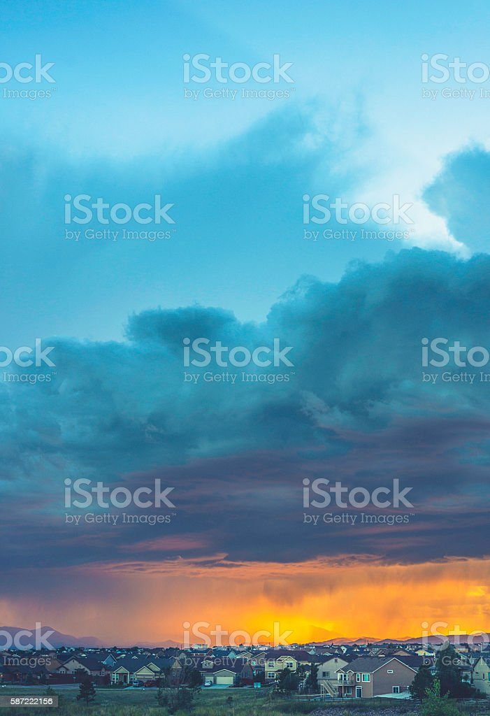 Thunderstorms hover over Colorado neighborhood at sunset stock photo