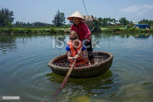 Hoi An, Vietnam - April 21, 2018: Caucasian woman learns to use Thung Chai round boat with guide in Hoi An