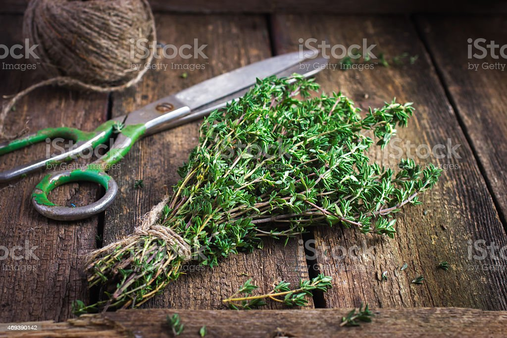 thyme bunch on an old wooden background stock photo