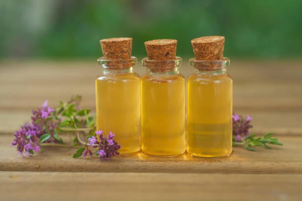 thyme essential oil in  beautiful bottle on table - oli, aromi e spezie foto e immagini stock