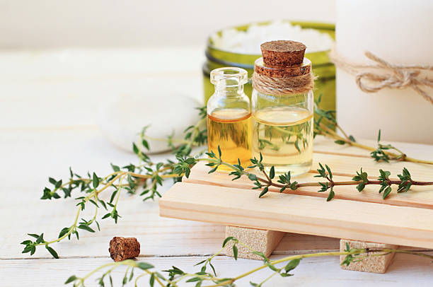 Thyme Herb Aromatherapy treatment. Botanic Spa. Thyme essential oil. Bottles with extract, fresh green plant leaves.  aromatherapy stock pictures, royalty-free photos & images
