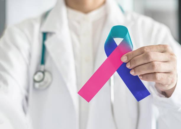 fita de conscientização câncer tireoide teal rosa azul laço simbólico da cor na mão do médico para apoiar o paciente com doença de tumor - cancer da tireoide - fotografias e filmes do acervo