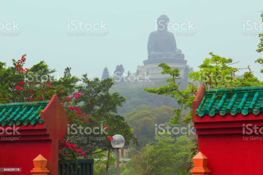 Tian Tan Buddha majestic bronze statue with the gates of Po Lin Monastery in the foreground. stock photo