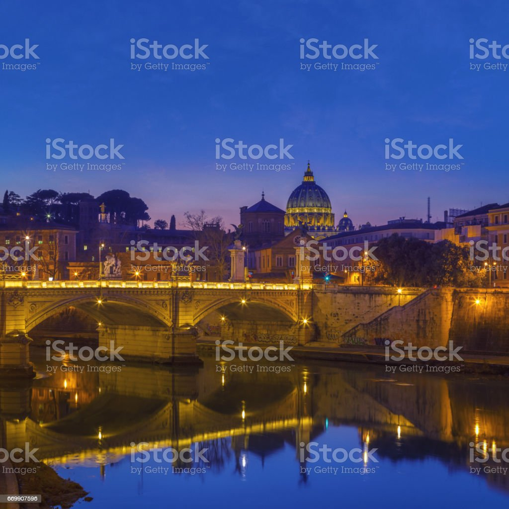 Tiber river in the night with Ponte Vittorio Emanuele II, the lit dome of St. Peter's Basilica in the background, Rome, Italy stock photo