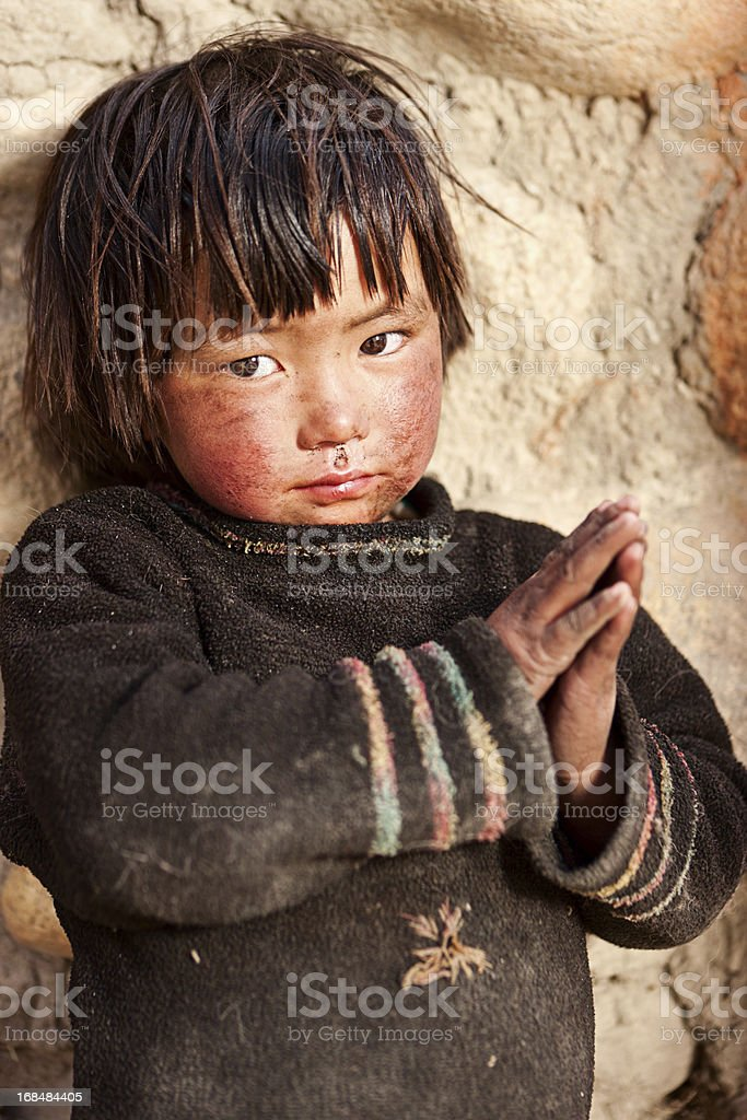 Tibetan child standing in front of the house. Mustang, Nepal. royalty-free stock photo