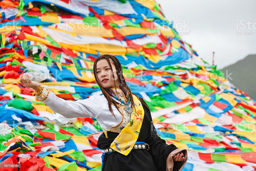 tibetan girl praying before the prayer flags stock photo