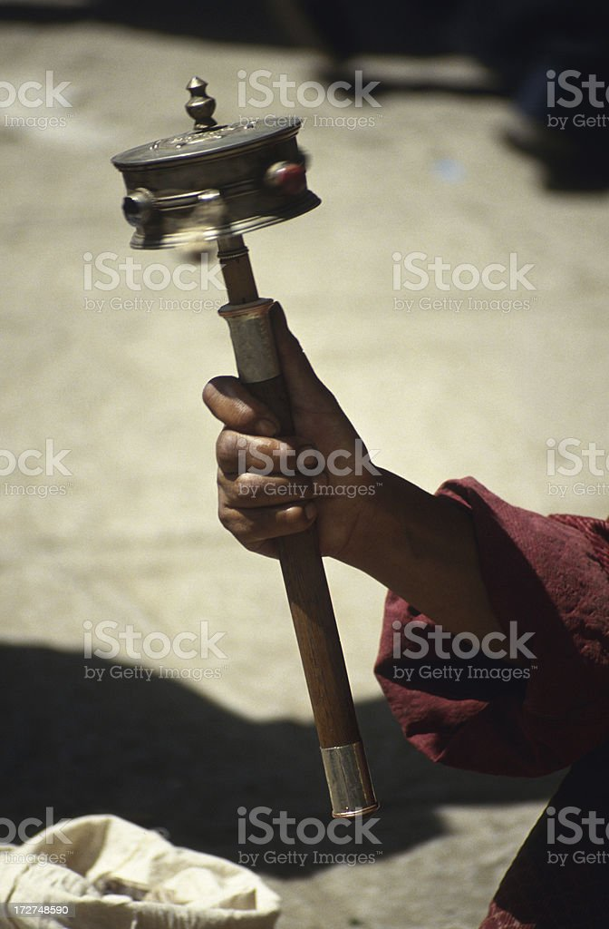 Tibetan holding a prayer wheel royalty-free stock photo