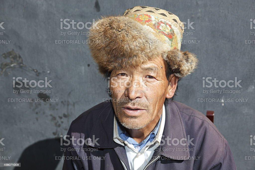 Tibetan Man in Fur Hat Mindroling Tibet stock photo