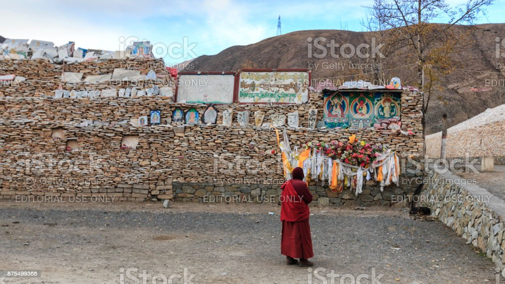 Tibetan monk praying in front of Mani stones at the Mani Temple (Mani Shicheng) wall with buddhist mantra Om Mani Padme Hum engraved in Tibetan in Yushu, China stock photo