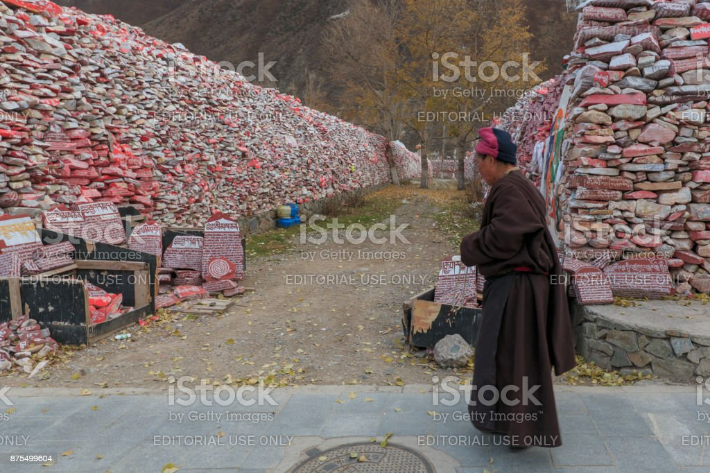 Tibetan monk walking in front of Mani stones wall with buddhist mantra Om Mani Padme Hum engraved in Tibetan in Yushu, China stock photo