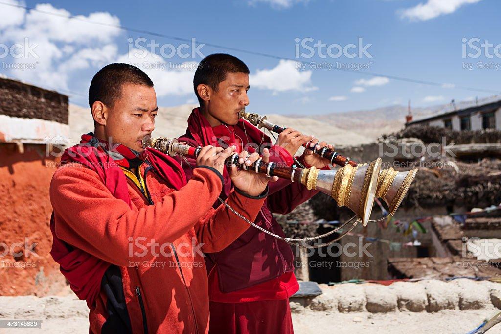 Tibetan monks playing buddhist horns in Upper Mustang stock photo