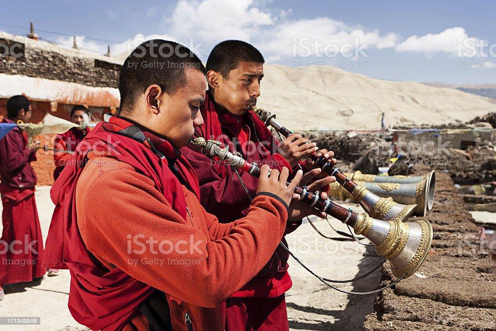 Tibetan monks playing buddhist horns stock photo