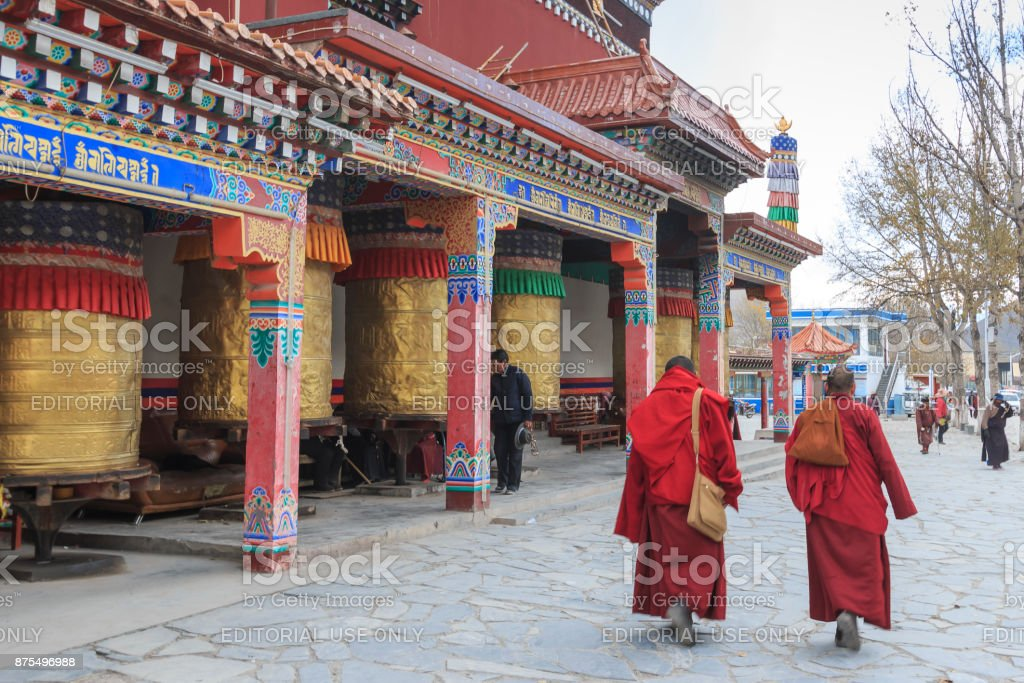 Tibetan people and monks walking around the Mani Temple (Mani Shicheng) a famous landmark in the Tibetan city of Yushu (Jyekundo), Qinghai, China. stock photo