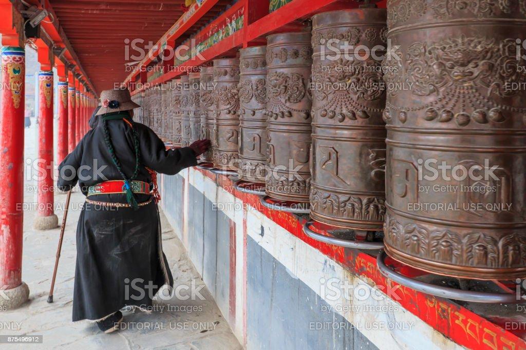 Tibetan people spinning the prayer wheels around Mani Temple (Mani Shicheng) a famous landmark in the Tibetan city of Yushu (Jyekundo), Qinghai, China. stock photo